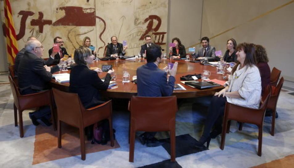 Imatge de la reunió del consell executiu. El president i els consellers mostren unes cartolines amb fragments de poemes que la consellera Borràs els ha repartit.