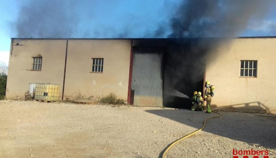 Els Bombers treballant en l'incendi en una nau agrícola de Tortosa.