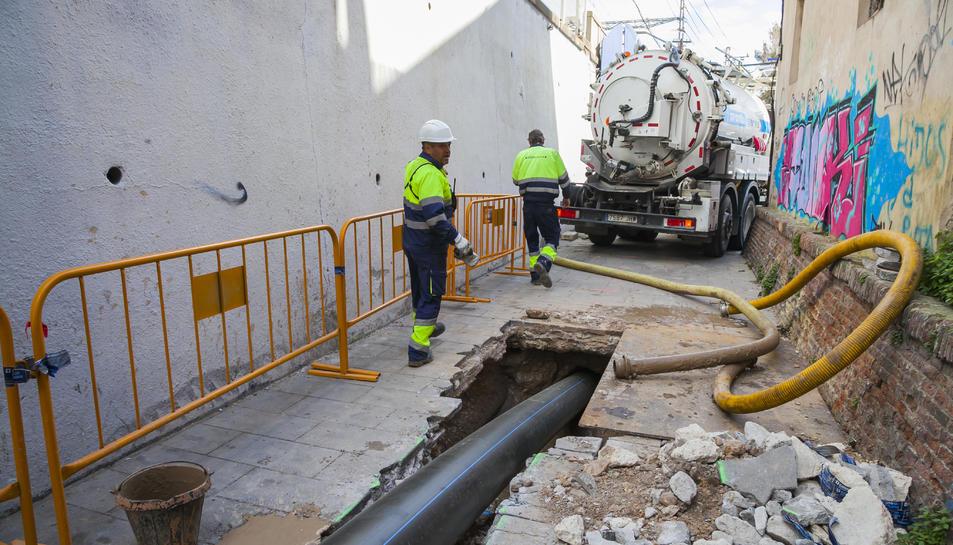 Operaris treballen en un dels punts de la canonada entre el carrer Sant Pere i les vies del tren.