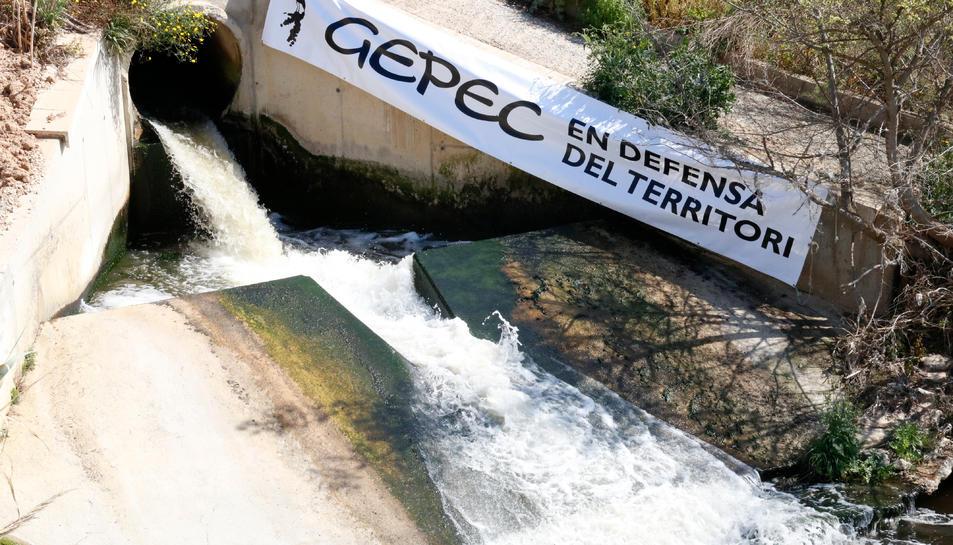 Imatge de la sortida de les aigües de la depuradora de Reus, amb un cartell de Gepec per denunciar que aquest cabal no es reutilitzi i se segueixi transvasant aigua del riu Siurana al pantà de Riudecanyes.