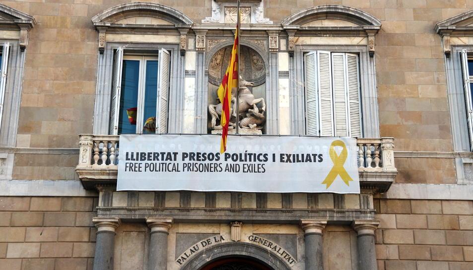 Part central de la façana del Palau de la Generalitat amb la pancarta amb el llaç groc penjats.