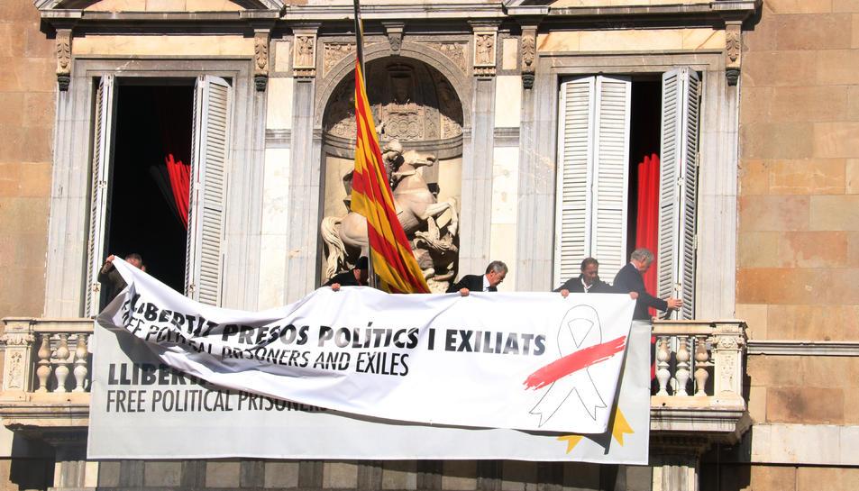 Treballadors del Govern afegeixen una pancarta damunt l'anterior, ara amb el llaç blanc i una franja vermella, al balcó del Palau de la Generalitat.