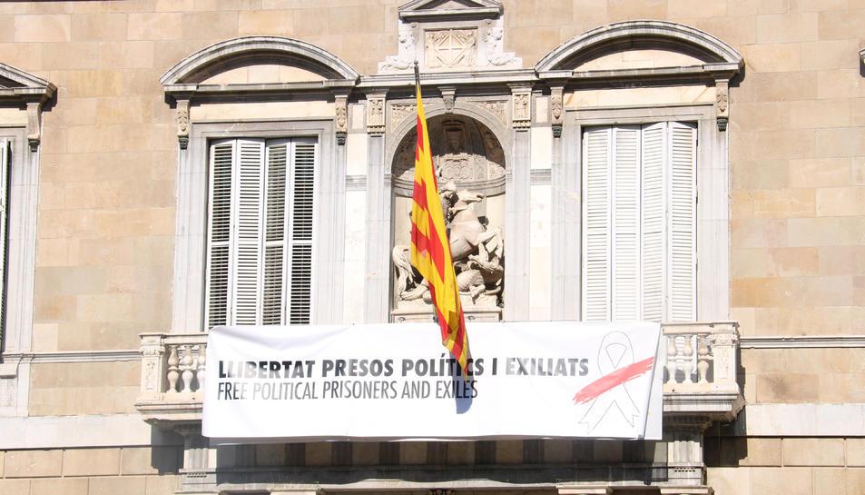 «Llibertat presos polítics i exiliats», diu la nova pancarta amb un llaç blanc amb una franja vermella, en comptes del llaç groc de la pancarta anterior.