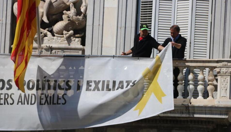 Dos treballadors retiren les pancartes del balcó del Palau de la Generalitat.