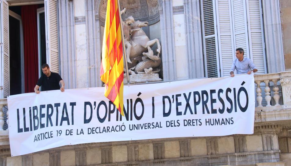 Membres de l'equip del president del Govern, Quim Torra, col·loquen la nova pancarta a la façana de Palau.