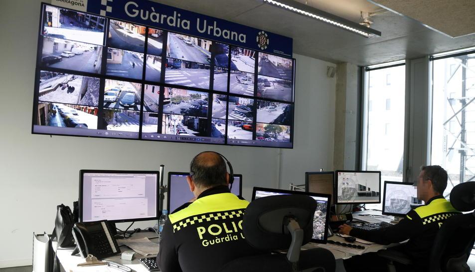 Dos agents de la Guàrdia Urbana de Tarragona treballant a la sala de control de la comissaria.