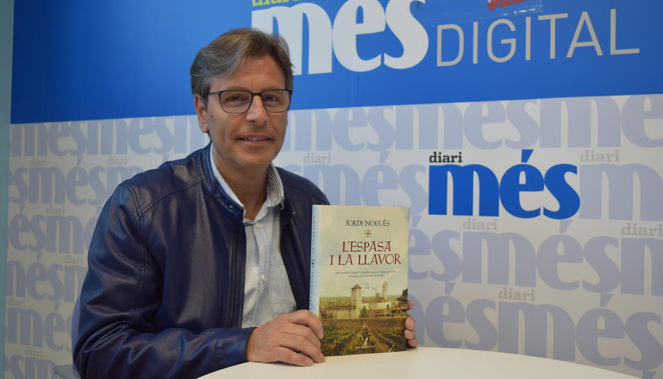 Jordi Nogués sosté a les seves mans un exemplar de la novel·la 'L'espasa i la llavor'.
