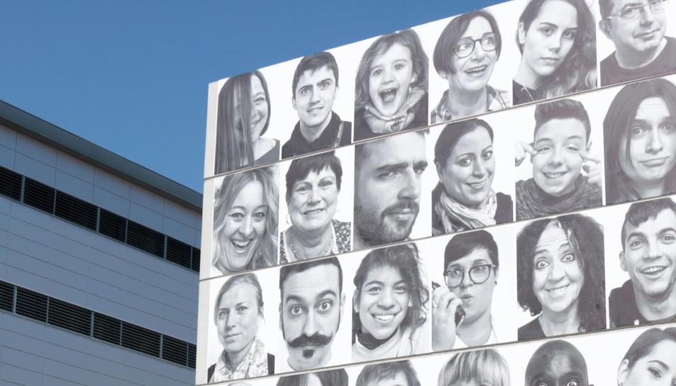 Un grup de joves passa per davant de la façana de Lo Pati on es troben enganxats los retrats de #mosmirem.