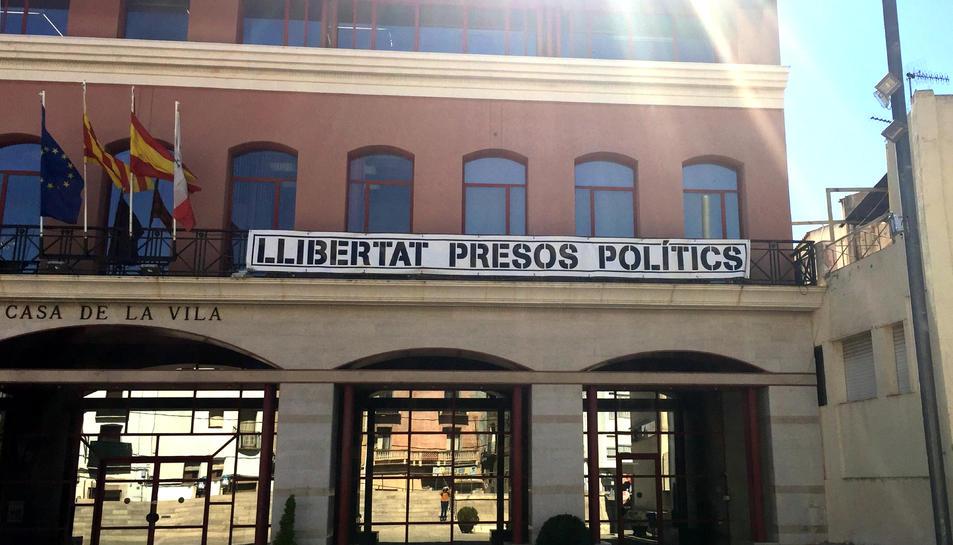 Pla contrapicat de part de la façana de l'Ajuntament d'Alcanar on encara hi ha penjada la pancarta en favor dels presos. Imatge del 27 de març del 2019 (horitzontal)