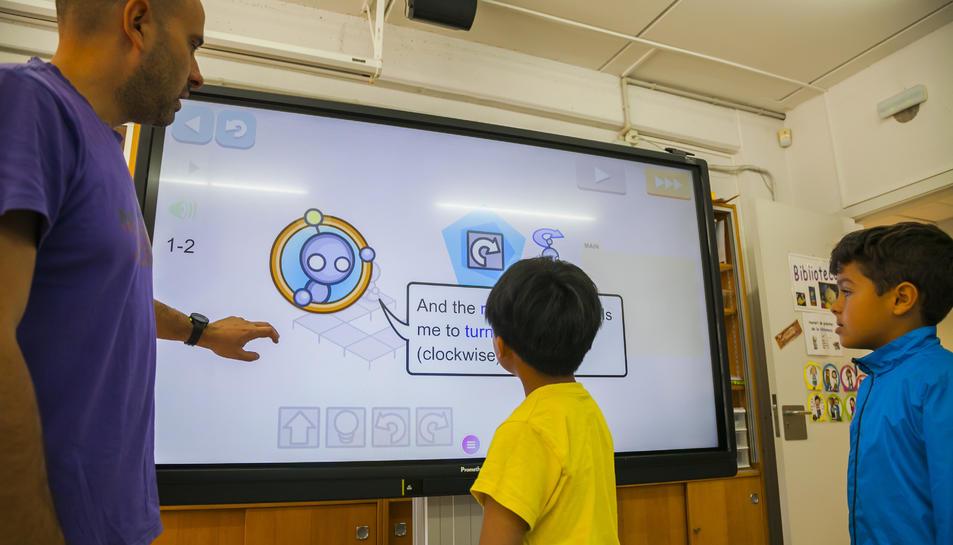 Moncusí explica a dos alumnes el funcionament d'un panel interactiu que ha incorporat l'escola.