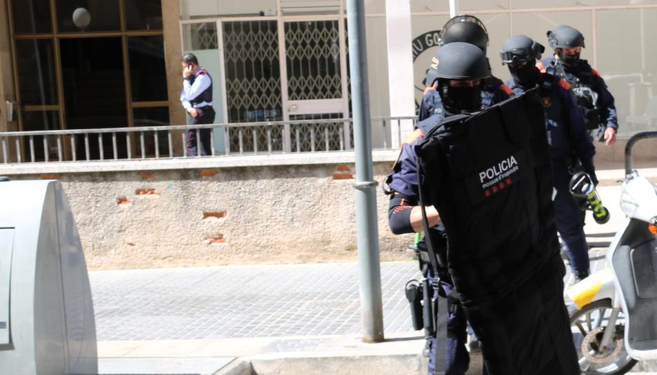 Agents ARRO dels Mossos d'Esquadra sortint del portal d'un bloc de pisos de Valls.