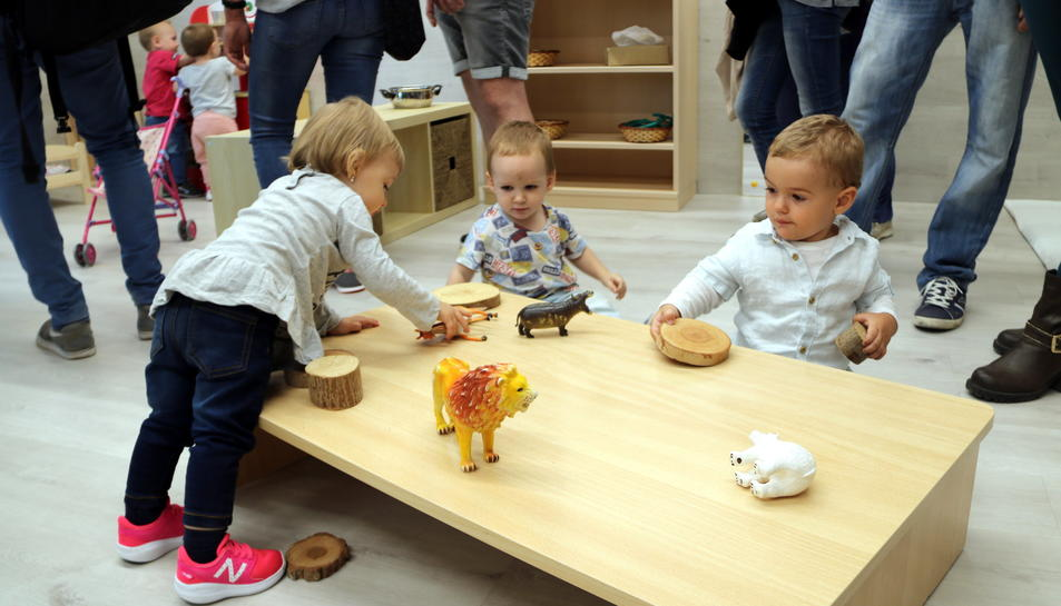 Tres nens que juguen en una taula d'una llar d'infants.