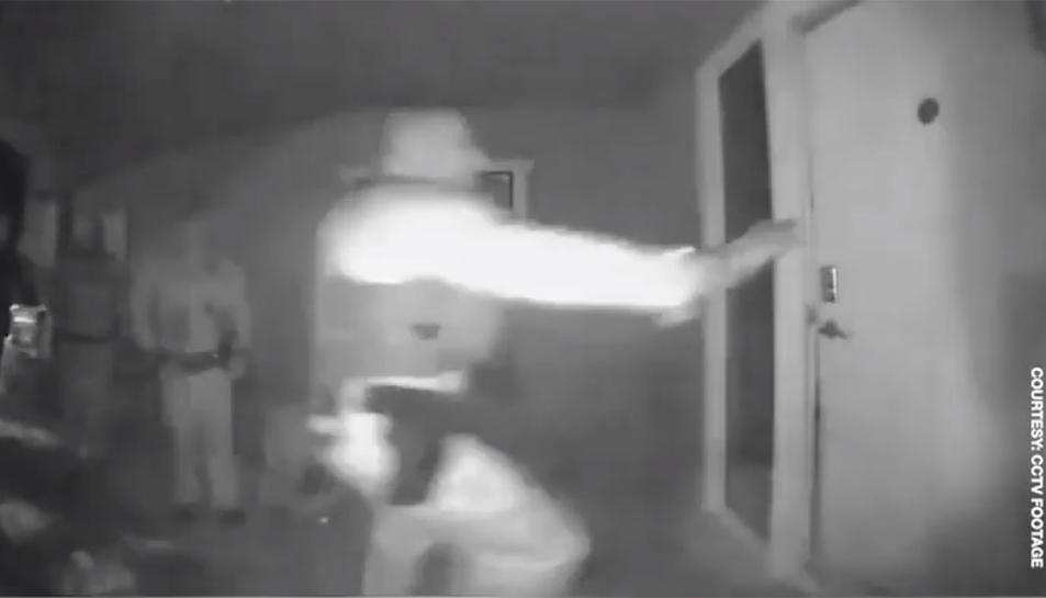 Un dels policies colpejant la porta de l'habitatge.