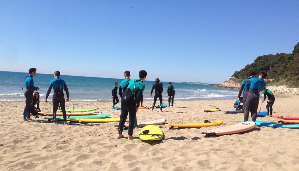 Imatge d'un grup d'alumnes en una classe de surf.