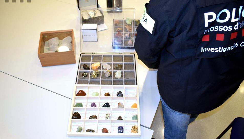 Un agent dels Mossos revisant part de les col·leccions de valor que l'agressor va robar a la víctima de la Sénia.