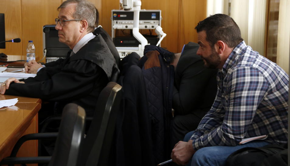 Pla tancat dels dos acusats, a la dreta i un d'ells tapant-se amb una jaqueta, a l'Audiència de Tarragona.