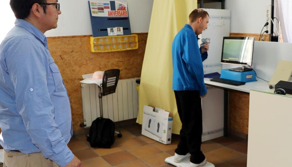 Un usuari provant el joc per a persones amb paràlisi cerebral, sobre la taula d'equilibri, observat per Julian Cristiano, un dels investigadors.