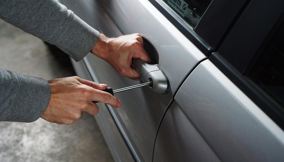 Un home intentant forçar el pany de la porta d'un vehicle