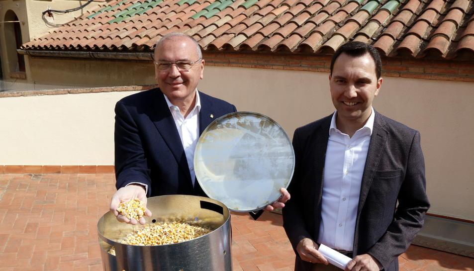 L'alcalde de Reus, Carles Pellicer, i el regidor de Medi Ambient, Daniel Rubio, al costat d'un dispensador de pinso anticonceptiu per a coloms que, durant uns dies, llençarà blat de moro.