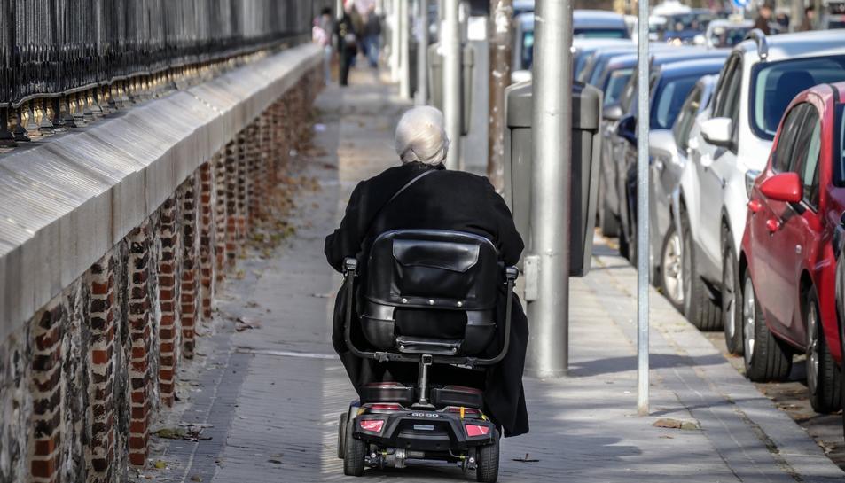 Imatge d'arxiu d'una persona circulant pel carrer amb una cadira elèctrica.