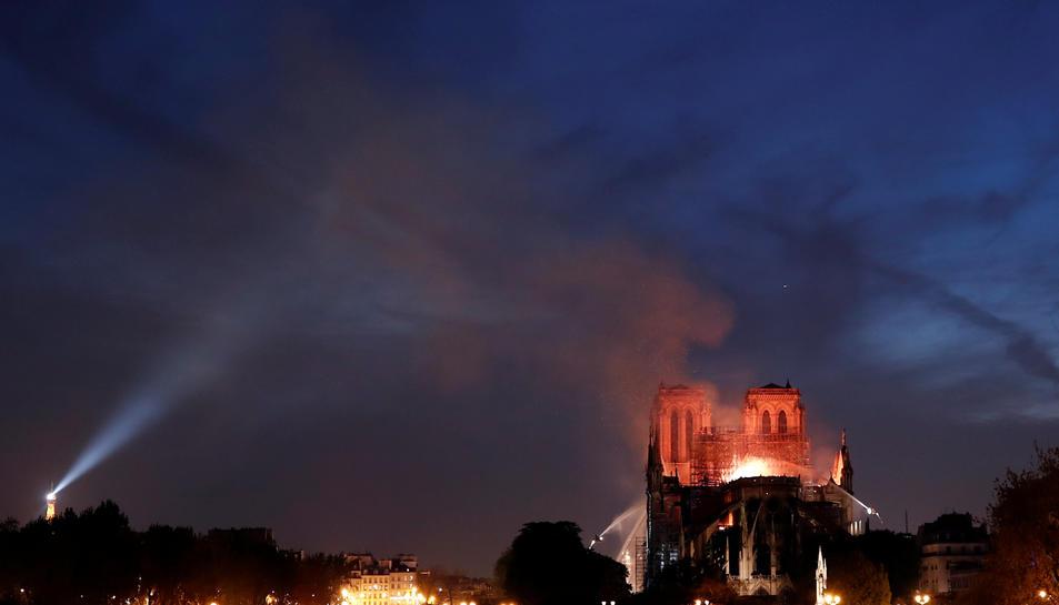 La Catedral de Notre-Dame de París en flames durant la nit, amb bombers remullant l'edifici per intentar salvar les torres.