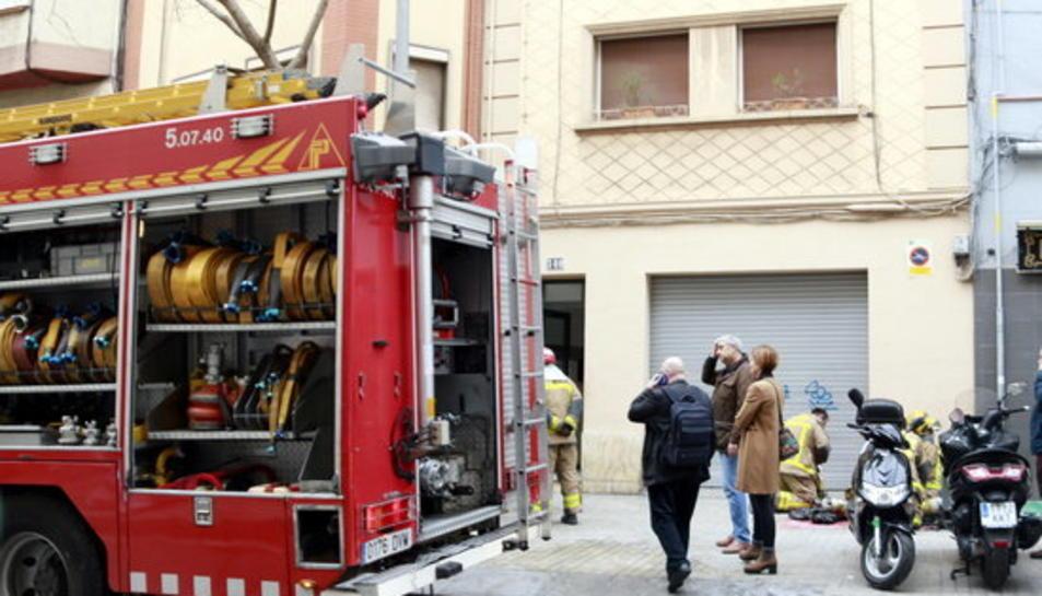 Un vehicle dels Bombers davant l'edifici on tres persones han perdut la vida en l'incendi d'un pis, a l'Hospitalet de Llobregat.