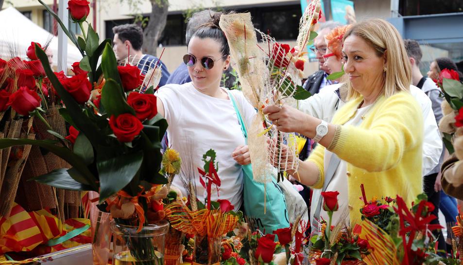 Image de dues dones comprant roses Durant la Diada de Sant Jordi a la Rambla Nova de Tarragona.