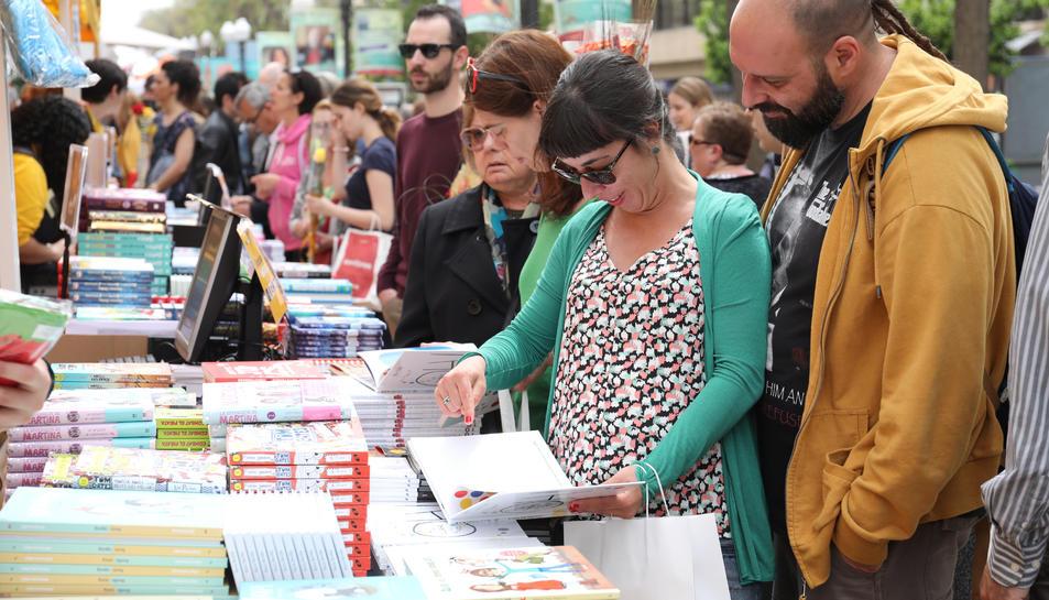 Diverses persones fullegen llibres durant la Diada de Sant Jordi a la Rambla Nova de Tarragona.