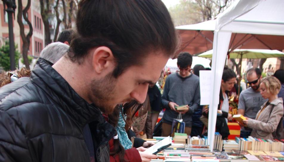 Un home remena una parada de llibres a la Rambla Nova de Tarragona, durant la diada de Sant Jordi. Foto del 23 d'abril del 2019 (Vertical).