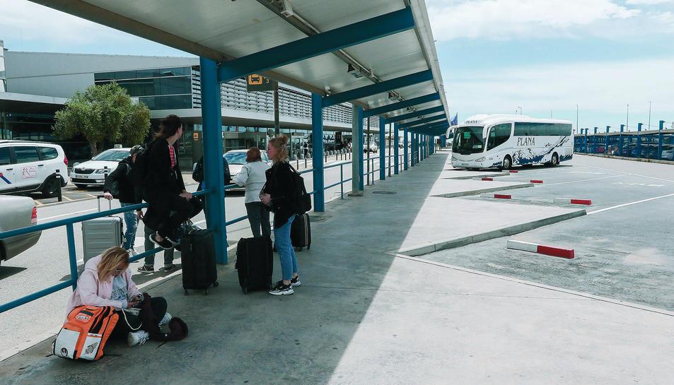 Passatgers esperen l'arribada d'autobusos interurbans a les andanes de l'aeròdrom.