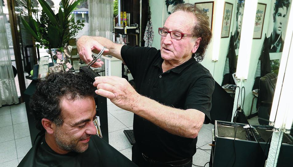El perruquer Jordi Gimeno, que té el local a la plaça Prim, atenent un client, ahir.