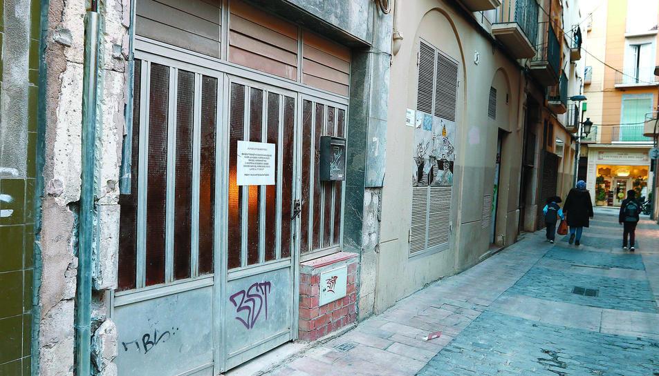 El cartell penjat a la porta de l'edifici, al carrer de la Concepció.