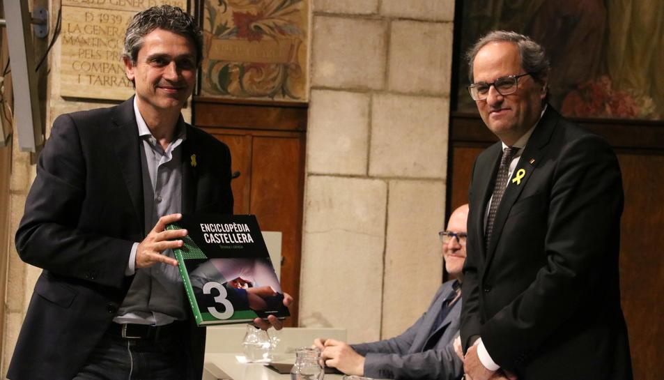 El president Quim Torra lliura al representant d'una colla castellera un exemplar del tercer volum de l'Enciclopèdia castellera.