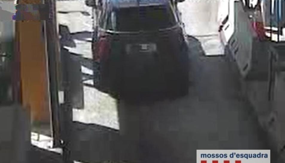 Pla general del vehicle passant pel peatge amb la matrícula tapada.