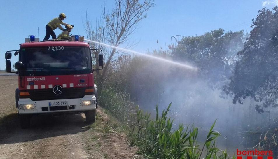 Un bomber amb la mànega treballant a l'incendi.