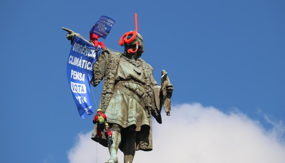 L'estàtua de Colom amb dos activistes despenjant una pancarta.