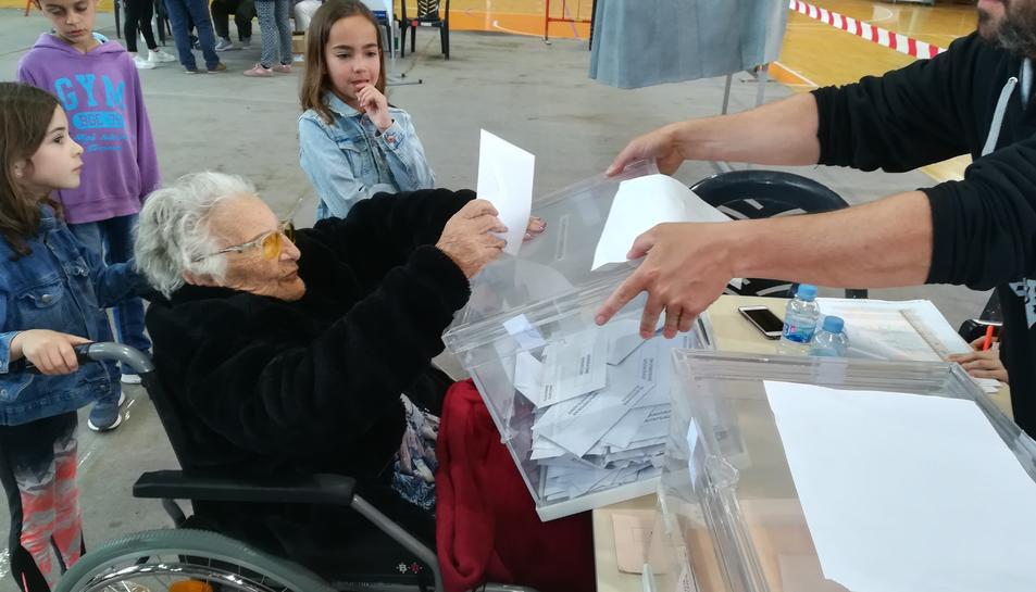 L'Amèlia Guardià de l'Arboç als seu 107 anys exercint el seu dret a vot, acompanyada de la besnéta, que agafa la cadira i el seu besnét.