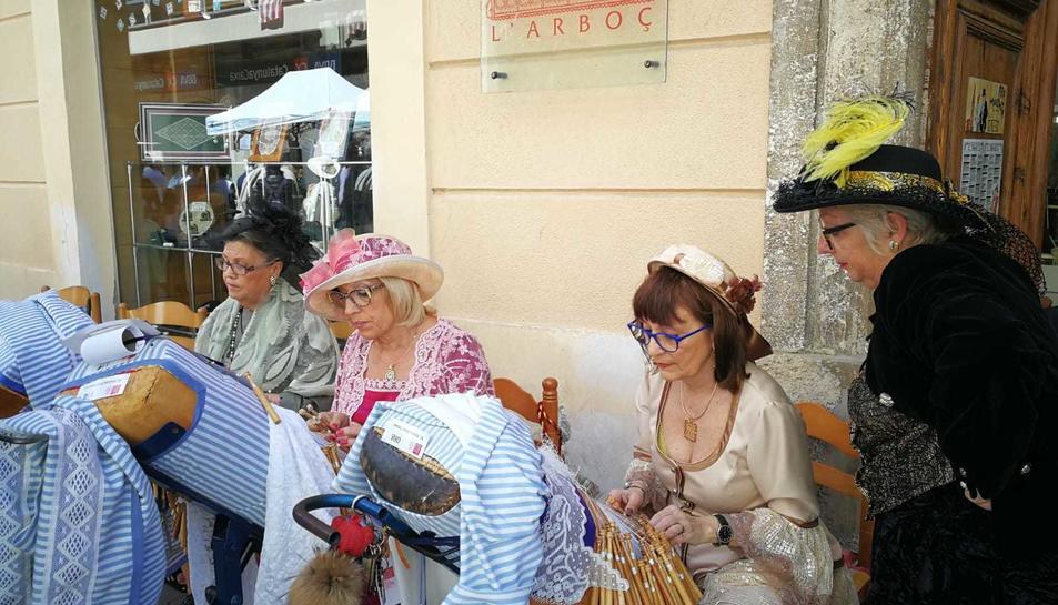 Dones vestides d'època mostraven l'art de la punta al coixí mentre els visitants passejaven per la fira.
