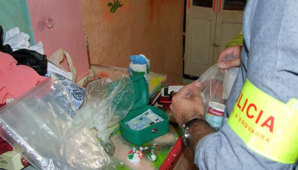 Un agent dels Mossos d'Esquadra inspeccionant les drogues i altres efectes intervinguts en un pis de Roquetes.