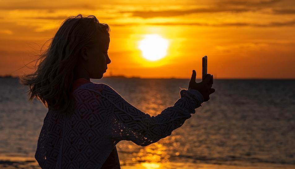 Una noia fent-se un selfie en un paratge natural.