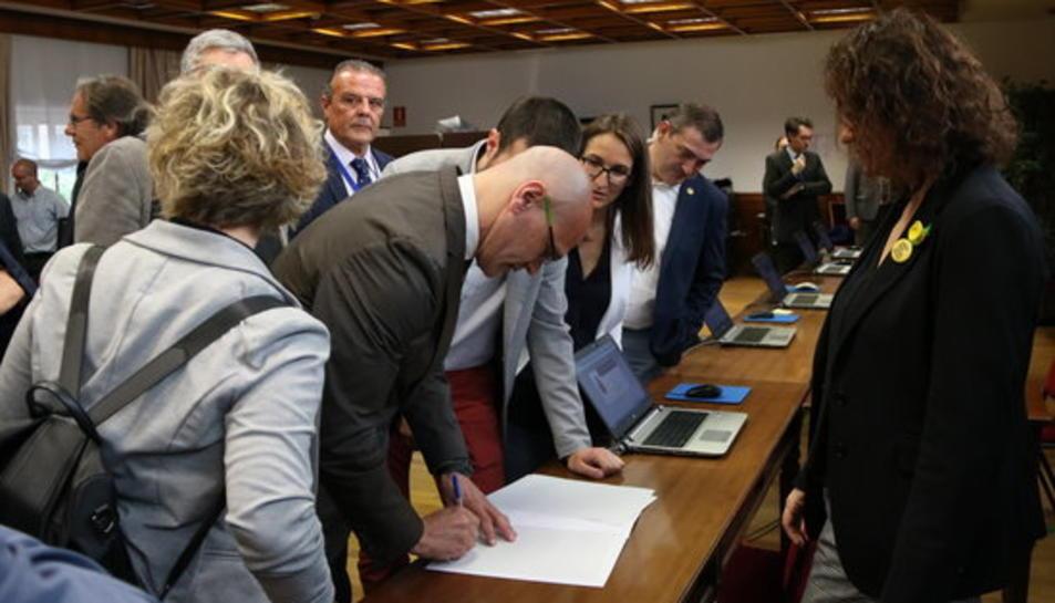 El senador electe d'ERC Raül Romeva signant un document durant el tràmit de recollida de l'acta de senador acompanyat d'altres senadors republicans.