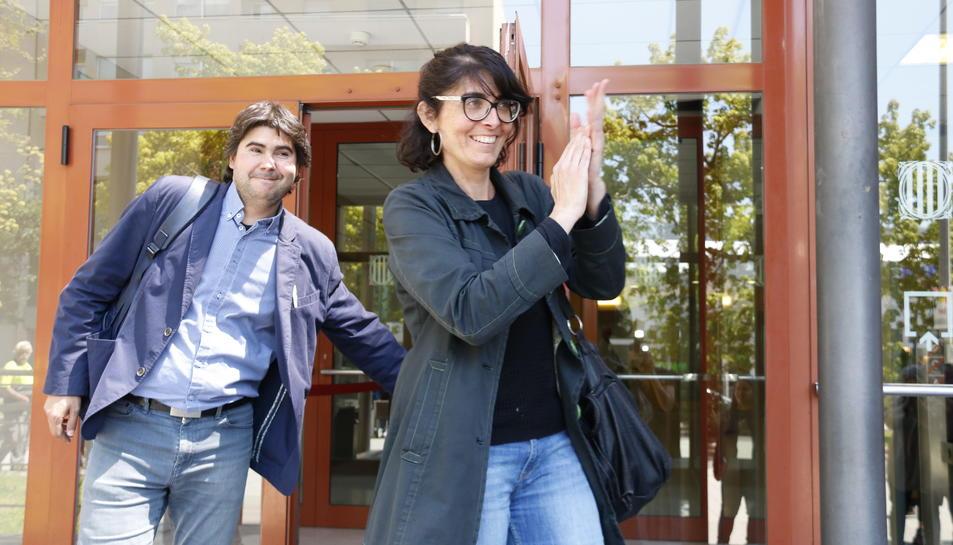 La candidata de la CUP de Reus, Marta Llorens, després de declarar als jutjats de Reus, somrient i aplaudint davant un grup de persones que li han donat suport, junt amb el seu advocat, Carles Perdiguero. Imatge del 21 de maig del 2018