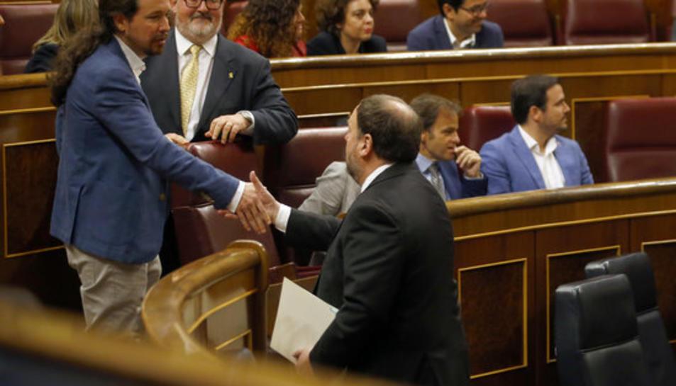 El líder de Podem, Pablo Iglesias, saluda el president d'ERC, Oriol Junqueras, durant la sessió de constitució del Congrés dels Diputats.