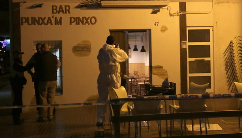 Un agent de la policia científica dels Mossos fent fotos de la façana del bar Punxa'm Pinxo de Sant Carles de la Ràpita el 13 de desembre de 2017.