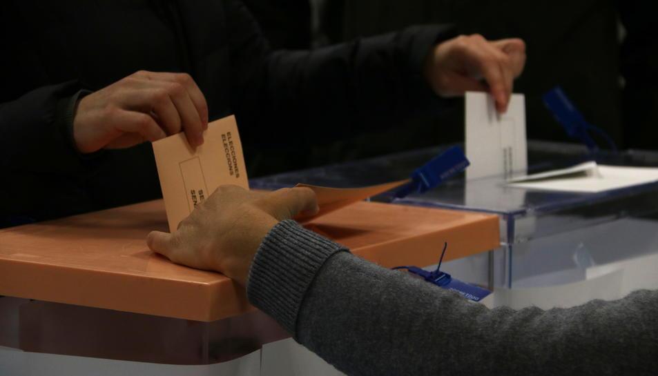 Pla detall d'una mà dipositant les paperetes de les eleccions al Congrés dels diputats i al Senat en una urna.