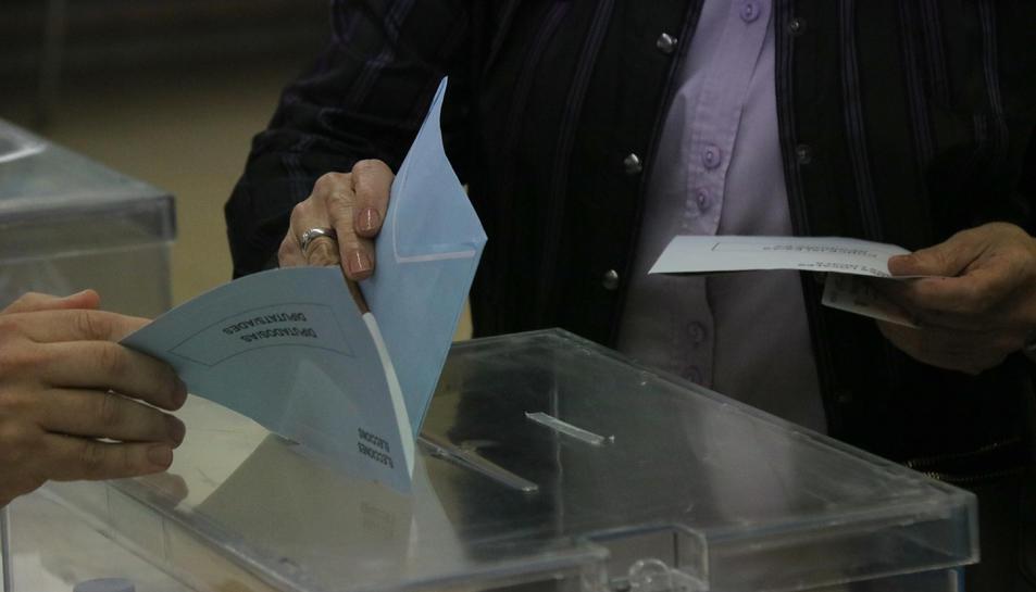 Instant en què una dona diposita el seu vot en una urna.