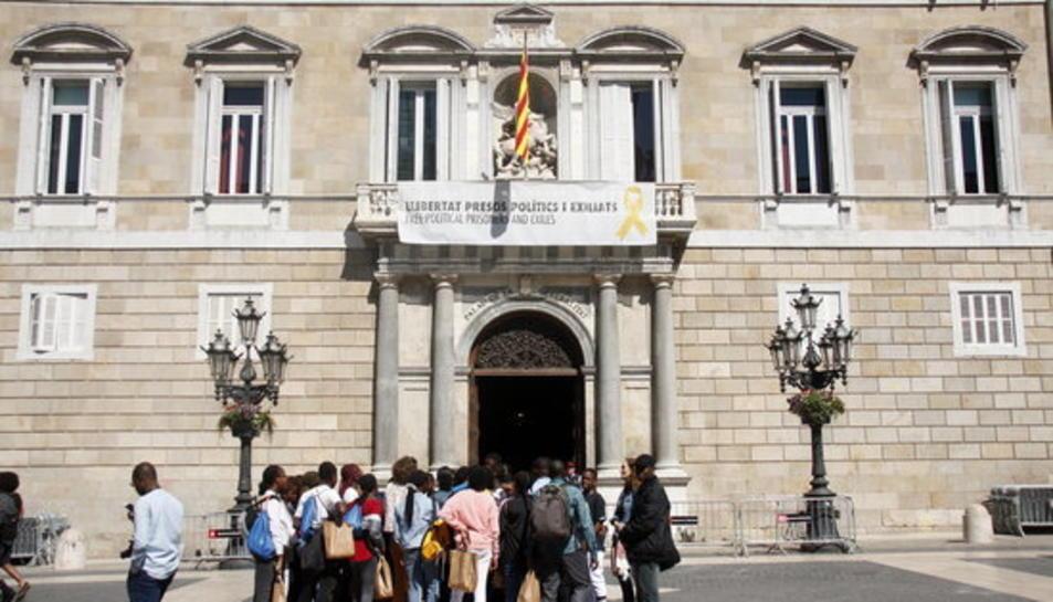 La façana del Palau de la Generalitat amb la pancarta restablerta i un grup de persones mirant la façana aquest 27 de maig.