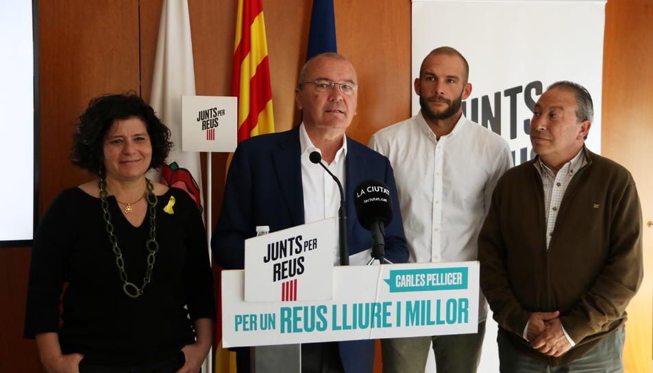 El cap de llista de Junts per Reus, Carles Pellicer, acompanyat de membres del partit en la roda de premsa per valorar pactes postelectorials.