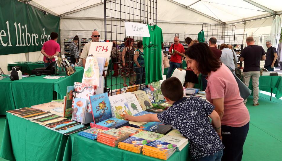 Compradors a la carpa de la Fira del llibre Ebrenc, ubicada a la plaça de Dalt de Móra d'Ebre.