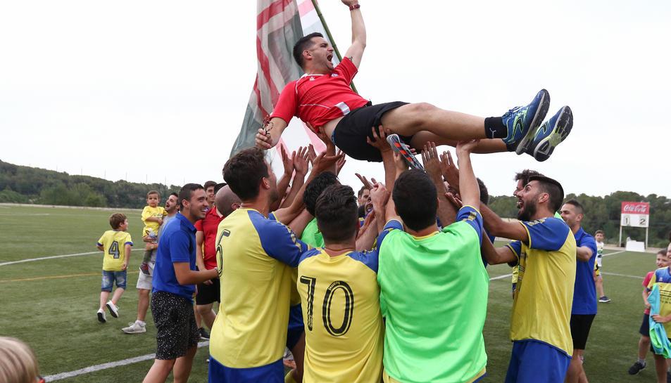 Els jugadors del Catllar celebrant l'ascens i mantejant al tècnic de l'equip.